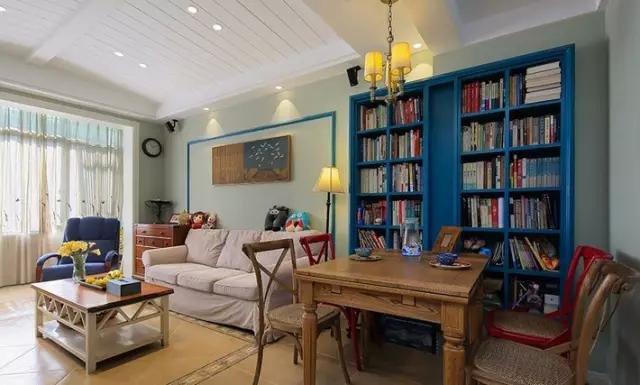 利用一整面墙的书柜划分区域,书柜颜色与客厅沙发,墙饰相互呼应,且图片