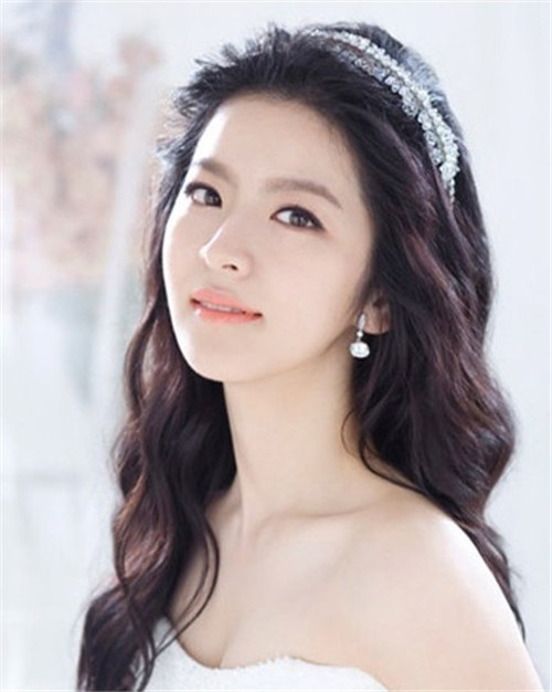 韩式新娘妆发型图片三:蓬松 这一种也比较挑头发,但造型师技术高的话一样可以选择哦,这一种也很漂亮,可以选择一些造型夸张的装饰物,例如华丽的王冠,或者礼帽,或者柔软的羽毛等,也可以戴上头纱。像图片那位新娘,一层层弄的蓬松,感觉就比较大气和华贵,这也比较适合大型的婚礼,中式,欧式这样富丽堂皇的婚礼,婚纱可以选择托长尾的,短婚纱就与其不搭了。