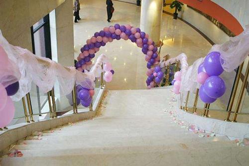 新娘自己就是那个最美丽的公主,紫色与粉色的气球拱门造型布置在楼梯