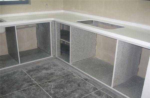 橱柜是烹饪间的标配,它可以让烹饪间变得更加的清爽整洁。大家每天都要在灶台上整理食材和烹饪食物,因此灶台的品质是至关重要的。那么厨房灶台的材质都有哪些呢?下面我们就一起来欣赏一些厨房灶台装修效果图,同时来了解下常用的厨房灶台材料。 厨房灶台装修效果图一  图中这款橱柜采用的是人造石灶台,白色的灶台搭配紫色橱柜充满了现代的时尚气息。相信大家在生活中都有见过人造石,它是用石粉加入人造纤维经过高温高压而制成的,它的主要特点就是绚丽多彩,人造石的表面是没有毛细孔的,它具有极强的耐污、耐酸、耐磨损等性能,并且很容易清
