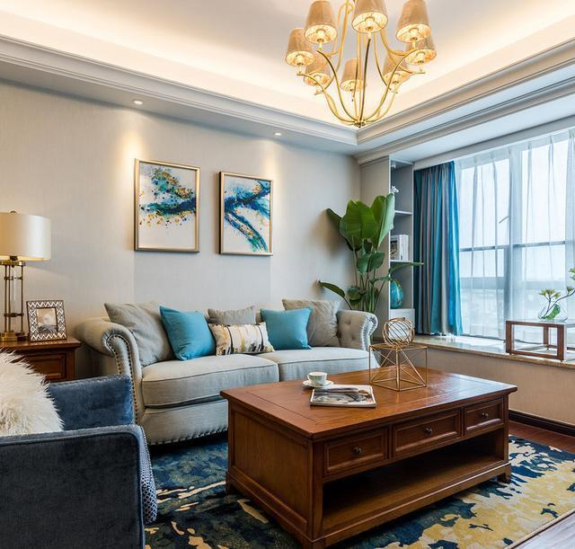 客厅沙发和茶几特写,沙发背景墙没做什么造型,就挂了两幅画,飘窗的