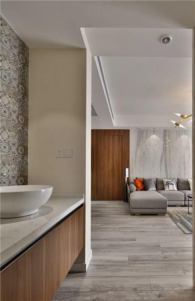 今天分享的是一套建筑面积118平米的简约风三居室案例,设计师在开放的客餐厅中,以灰色的木质感为主,搭配白色的柜子、吊顶等,来构造出这样一个轻松而又舒适的氛围,特别是客厅的设计,让人感觉非常的帅气。   入户没有玄关走廊的户型,利用餐厅那侧的墙面做了鞋柜,整个客餐厅地面都铺贴了相同款式的木地板,整体感更强。  客厅的电视背景墙和沙发背景墙也做了和地面相同的造型,整体复古木质感的设计,让客厅显得格外的帅气、时尚。  餐厅位于入户门的另一侧,在餐桌椅的边上还设计了一个岛台,把水槽放在这里,方便吃饭前后洗手,还可